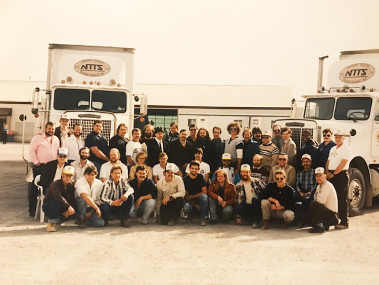 80s-Class of NTTS students posing in front of trucks