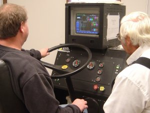 A student and driving instructor training in a driving simulaltor machine.